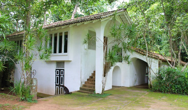 Lunuganga Sri Lanka gate house exterior white building with archways and trees