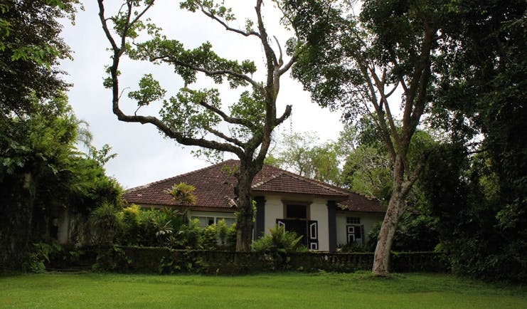 Lunuganga Sri Lanka main house exterior white bungalow and gardens