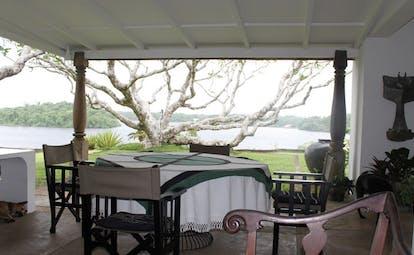 Lunuganga Sri Lanka terrace seating overlooking tree garden and lake