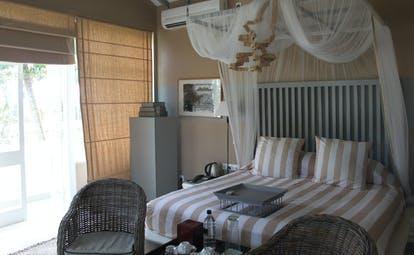 Bedroom with double bed, drapes and arm chairs
