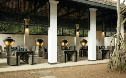 Outdoor dining terrace beneath a veranda with tables and chairs set up for dining
