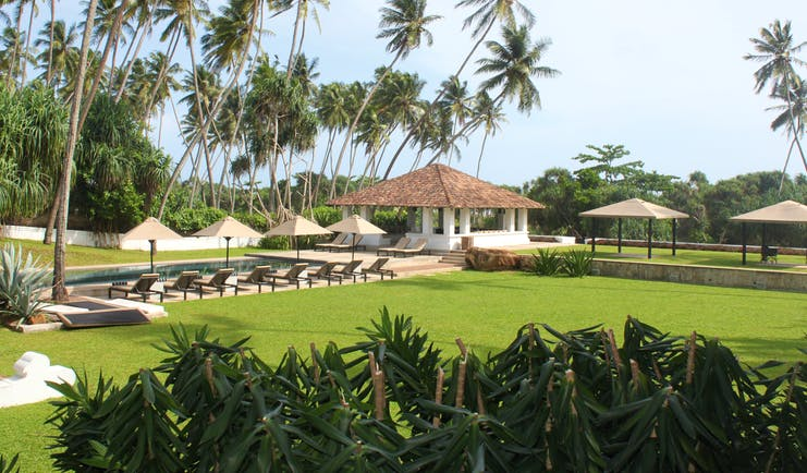 View of the gardens from the hotel with sunloungers and pool in distance