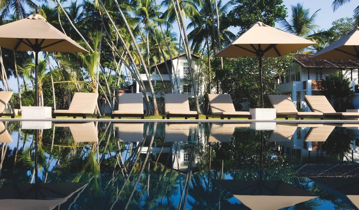 Pool view with beige sunloungers and umbrellas on the pool edge