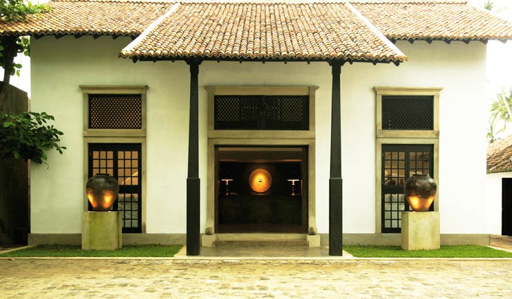 Paradise Road The Villa Bentota Sri Lanka entrance white building with gold urns