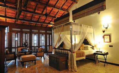 Reef Villa and Spa main house suite, canopied bed, antique furniture, elegant decor