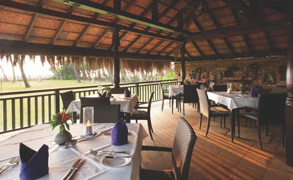Reef Villa and Spa restaurant, tables and chairs under thatched roof, rustic building overlooking gardens
