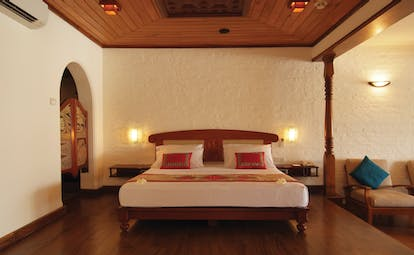 Deluxe suite room with large double bed, wood pannelled ceiling and floors and armchairs