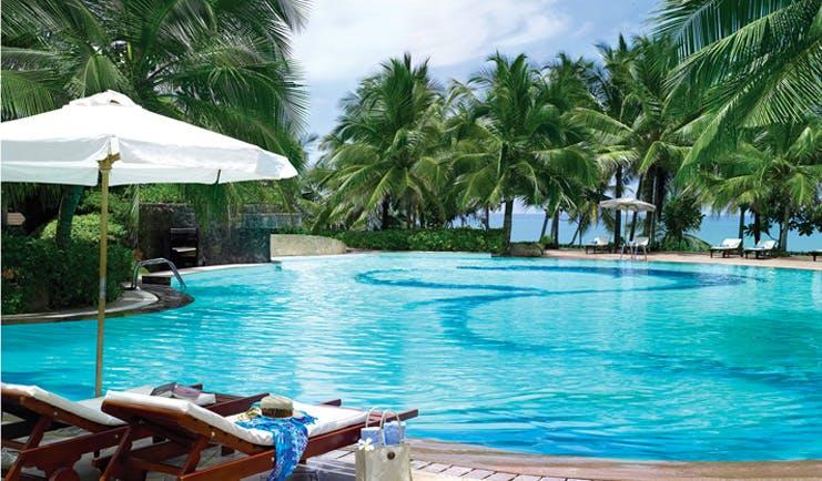 Taj Bentota Sri Lanka outdoor pool palm trees ocean view sun loungers