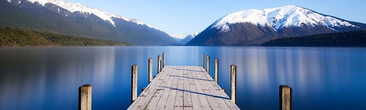 Wooden jetty into calm blue lake with snowy mountains in distance