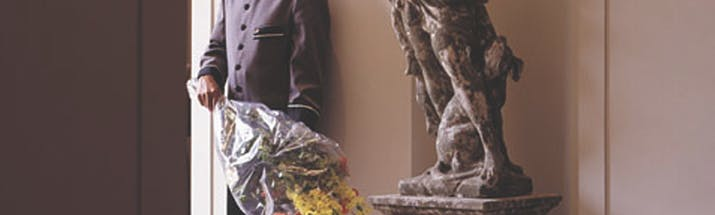 Man in hotel uniform standing next to statue with bouquet of flowers