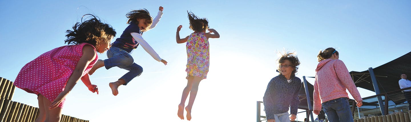 Children on a trampoline jumping with different dresses and clothes