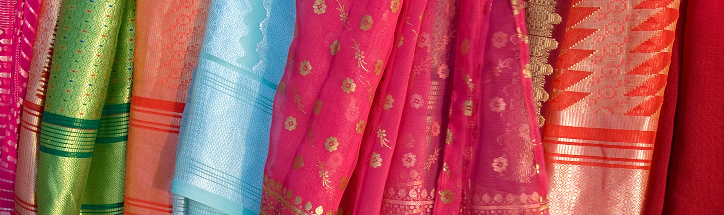 Silk material in shades of red and pink hanging up in Sri Lanka