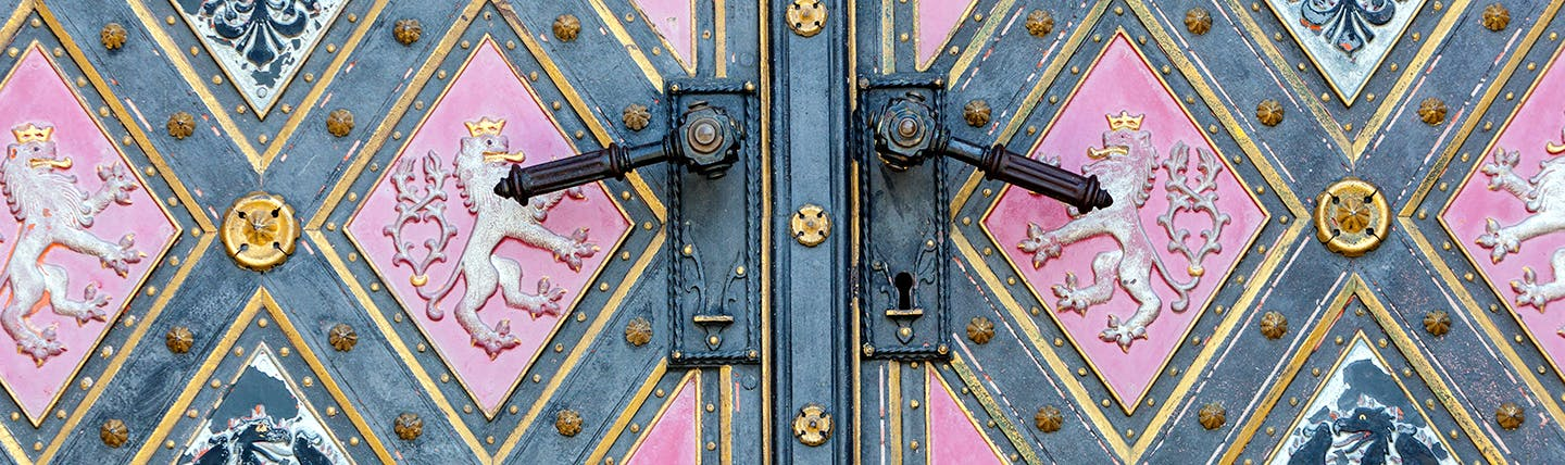 Ornate pink and grey doors of two-tailed lion and eagle at Vysehrad Prague
