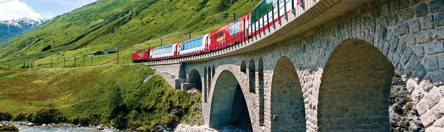 Red train with large windows on bridge in summer mountain landscape