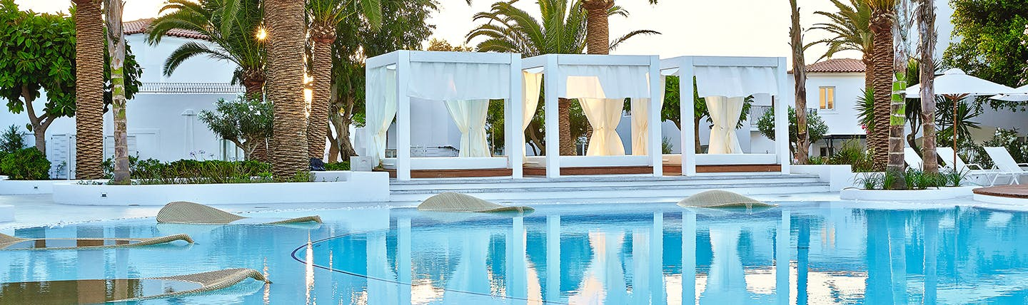 Blue swimming pool surrounded by large white canopy day beds and palm trees at Grecotel Caramel