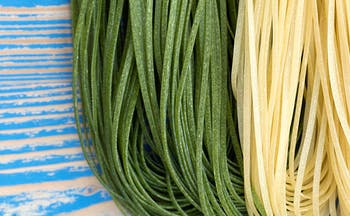 Green, white and red thin pasta strands resembling Italian flag