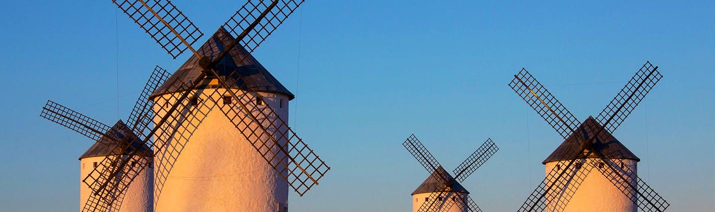 Four white windmills in the sun in La Mancha