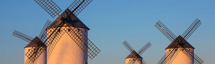 Four white windmills in the sun in La Mancha
