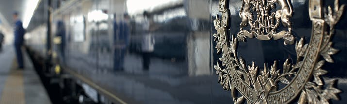 Silver embossed logo on side of the blue Orient Express train