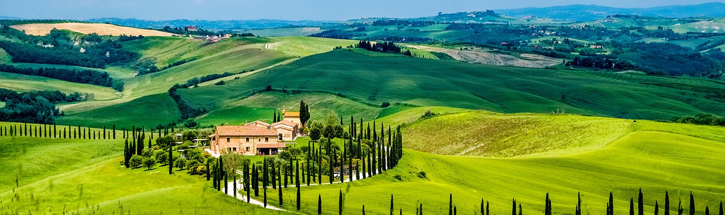 Scenic view of Tuscan landscape with green rolling fields, a farmhouse and Cypress trees
