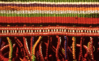 Woven mat in colours of ochre, red, orange and some green stripes