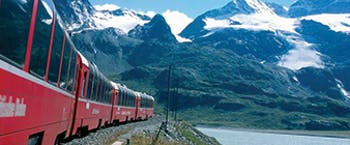 Red train with large windows with snowy mountains in background