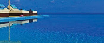 Deep blue infinity pool with sun loungers at Velassaru Maldives