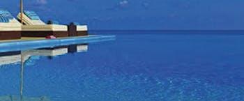 Deep blue infinity pool with sun loungers at Velassaru Maldives